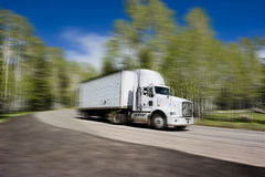 Truck in motion. Truck on highway - on a background of blue sky and trees Royalty Free Stock Photography