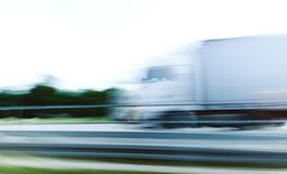 Truck in motion defocused security safety concept. In motion silhouette of white electric truck hauling on the autobahn highway in Germany Stock Image