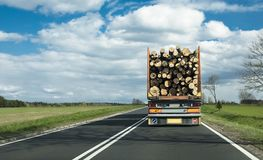 A truck on motorway transporting logs. A lorry on motorway transporting logs, surrounded by fields and clouds stock photography