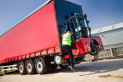 Truck Mounted Forklift. Portable Forklift Offloading from truck trailer stock images