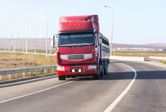 Truck moves on a highway. Front view. Red truck moves on an empty highway. Front view Stock Photo