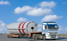 Truck moves huge industrial construction. A truck moves huge industrial construction Stock Photos