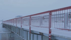 Truck Moves  on Snowy Bridge in Arctic. Big truck moves fast on new snowy bridge with red metal guardrail above Arctic circle in Russia stock video footage