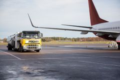 Truck Moving By Airplane On Runway. Truck moving by commercial airplane on wet runway stock photo