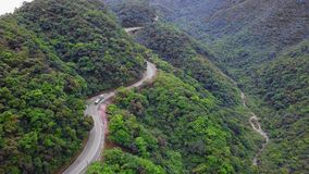 Truck Moving along Curved Serpentinous Road among Green Lush Forest Trees in Taiwan. Aerial View. Shot with a DJI Mavic fps 29,97 4k stock video