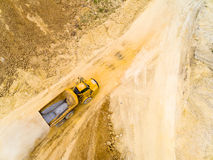 Truck on muddy road. Aerial view of truck on muddy road on a construction site. Heavy industry from above. Industrial background from devastated landscape royalty free stock photo