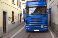 Truck in a narrow road. A big truck tries to pass through a village driving in a narrow road Royalty Free Stock Images