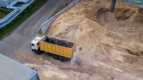 Truck near a pile of sawdust, the view from the drone stock images