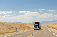 Truck on Nevada desert highway. Head on view of semi-trailer truck travelling on remote highway in Nevada desert, U. S. A stock photography