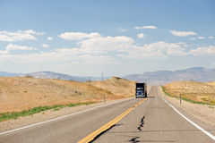 Truck on Nevada desert road. Head on view of semi-trailer truck driving on highway through Nevada desert landscape, U. S. A royalty free stock photo