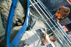 Truck operator pouring cement into crane bucket Royalty Free Stock Image