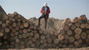 The truck with an orange body is going pass builder in a white helmet and red jacket. Boss of workers is standing on the pile of logs with documents in his stock footage