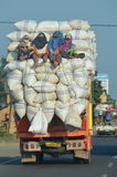 Truck overloaded with rice sacks. A unique photos of an overloaded truck carrying rice from the mill to the market. You can see the worker near the top of the Stock Photo