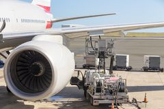 Truck parked under an aircraft wing refuelling. Truck parked under an aircraft wing re-fuelling the tanks with aviation fuel through an open flap with a turbo Stock Photo