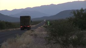 Truck pasing by in the evening. USA - JUNE 2009: Various shots of road traffic on vast highway. Longest bicycle competition over United States of America - RAAM stock footage
