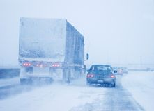 Truck and Passenger Car in Whiteout Driving Condit. A snow covered transport truck and a passenger car driving in almost whiteout conditions in Canada Royalty Free Stock Images