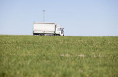 Truck passing by on a green agricultural field Royalty Free Stock Photography