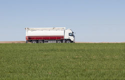 Truck passing by on a green agricultural field Stock Image