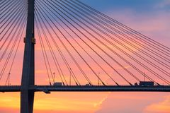 Truck and pickup truck crossing suspension bridge at sunset. Col stock photography