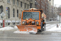 Truck with plow cleans snow on the street, New York City Stock Photo