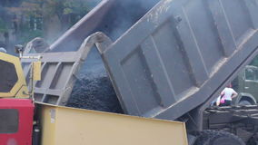 Truck pours the hot asphalt to the asphalt laying machine stock video footage