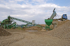 Truck and quarry conveyor. Truck unloading gravel into quarry conveyor Royalty Free Stock Photography