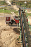 Truck and quarry conveyor, vertical. Truck passing by a quarry conveyor after unloading gravel Royalty Free Stock Images