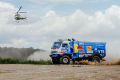 truck rally truck KAMAZ on dust road with a flying helicopter Stock Photos