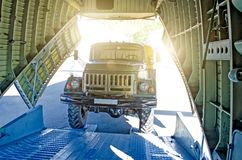 Truck on the ramp rides into the cargo area of the aircraft. Royalty Free Stock Photo