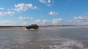 Truck rides across the lake. Truck Crossing the River. Old Soviet car runs on water. Saline salt lake Baskunchak stock footage