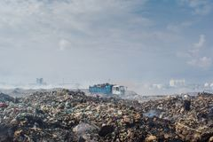 Truck riding at the garbage dump full of smoke, litter, plastic bottles,rubbish and trash at tropical island. Truck riding at the huge garbage dump full of smoke royalty free stock image