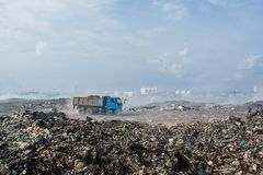 Truck on the road at the garbage dump full of smoke, litter, plastic bottles,rubbish and trash at tropical island. Truck on the road at the huge garbage dump royalty free stock photos