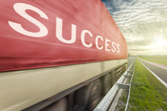 Truck on road in motion blur with success text. Red truck speed driving in motion blur on the freeway towards the setting sun. Business concept for the success Royalty Free Stock Photos