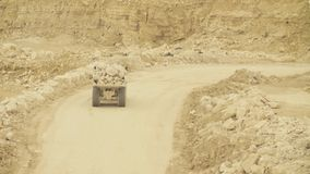Truck on a road in quarry carring stones. Truck carring stones on a road in a quarry stock video footage