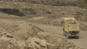 Truck on a road in quarry carring stones. Top view of a truck carring stones on a road in a quarry stock video footage