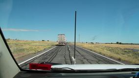 A truck on a road shot. A long shot of a truck on a road stock footage