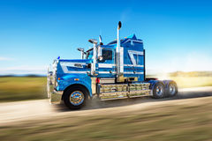 Truck on the road with speed blur. Truck on a dirt road with blue sky and speed blur going fast through a country road in dusty conditions royalty free stock images
