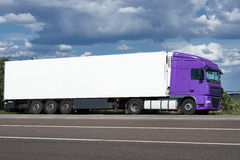 Truck on road with white blank container, blue sky, cargo transportation concept Royalty Free Stock Images