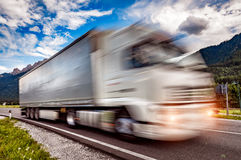 Truck rushes down the highway in the background the Alps. Truck Royalty Free Stock Photos