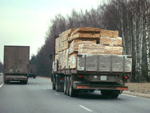 Truck with sawn timber cargo i. N motion on public road in a dark spring day Royalty Free Stock Photo