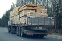 Truck with sawn timber cargo i. N motion on public road at dark spring day Stock Image