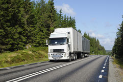 Truck on scenic country highway. Truck driving on a scenic country highway, trees and forest Royalty Free Stock Images