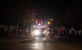 Truck with Seuss monster lights up nighttime street as people pr Royalty Free Stock Photos