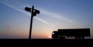 Truck with sign. Silhouette of articulated freight vehicle against dramatic sky, with signpost royalty free stock photos
