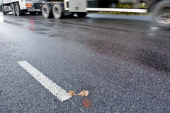 Truck on slippery road. Truck driving on treacherous and slippery road due to rain or frost Stock Photos