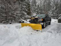 Truck snow plow clearing a parking lot after storm Royalty Free Stock Image
