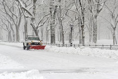 Truck with snowplow clearing road during snowstorm Stock Photo