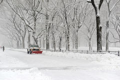 Truck with snowplow clearing road during snowstorm Royalty Free Stock Photo