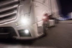 Truck speeding with lights on at night Stock Image