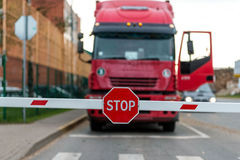 Truck standing at the barrier with a STOP sign. Stock Images